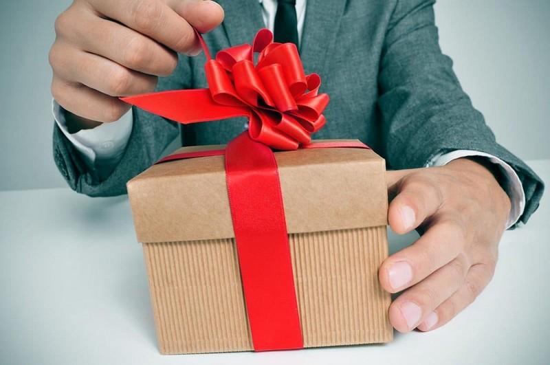 мужчина открывает новогодний подарок